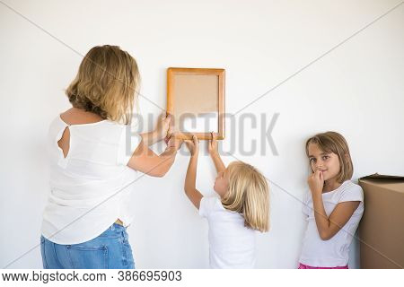 Lovely Girl Putting Frame On White Wall With Help Of Mom. Cute Daughter Hanging Blank Picture. Her S