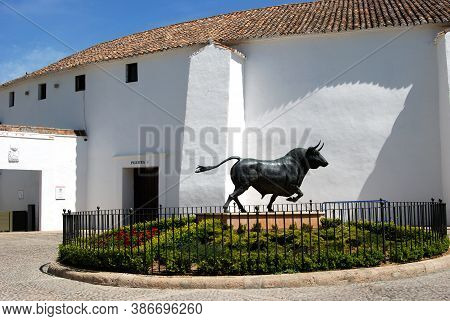 Ronda, Spain - May 5, 2008 - Bull Statue In A Flowerbed With The Bullring To The Rear, Ronda, Malaga