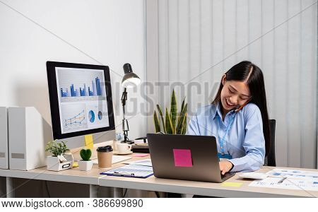 Asian Businesswoman Talking On The Phone And Working On A Laptop With A Cheerful And Happy Smile Whi