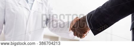 Partial View Of African American Man Shaking Hands With Doctor, Panoramic Shot