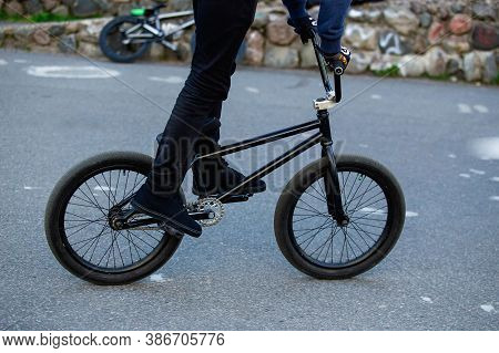 Bmx Rider On Black Bmx In Skatepark Close-up. Street Male Sports Outdoor Activity Concept