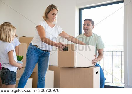 Beautiful Blonde Mother Putting Carton Box On Another One. Happy Family With Two Daughters Moving To