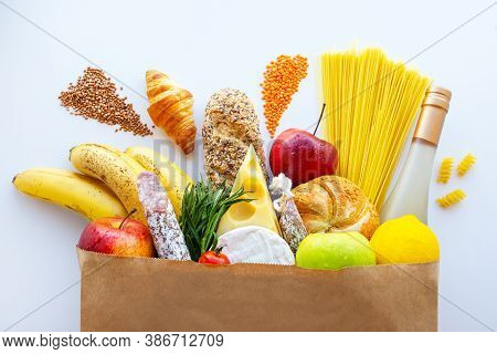 Full paper bag with healthy food.Supermarket food concept.Cheese, bread, fruits, vegetables, sausage