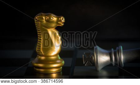 Checkmate Gold Knight Defeats Silver King On Black Background, Chess Board Game Concept Of Business