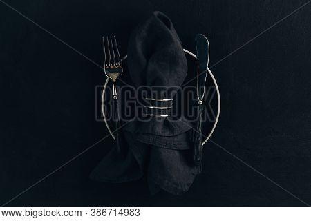 Elegant Black Table Setting: Plate, Napkin And Silverware Over Black Background.