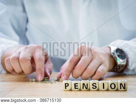 Closeup Wooden Block Written Pension Against Senior Man Hand Putting Coin Into Piggy Bank To Saving