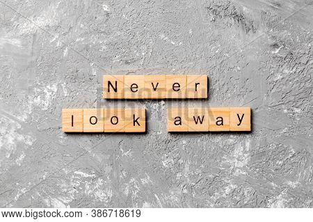 Never Look Away Word Written On Wood Block. Never Look Away Text On Cement Table For Your Desing, Co