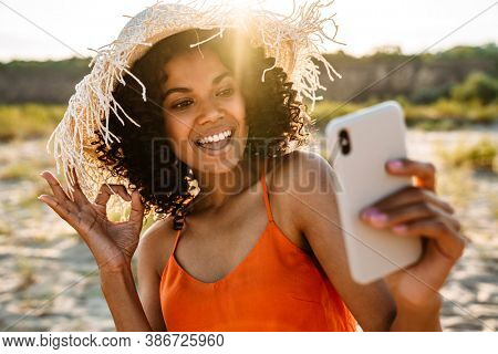 Image of pretty smiling young african woman taking a selfie by mobile phone at the beach outside while showing okay gesture
