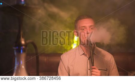 Young Blond Man Smoking Hookah And Producing Rings Of Smoke. Media. Magicical Smoking. Young Man Rel