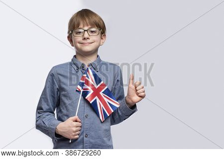 Teenager Holding A Flag Britain In His Hands And Shows Gesture Of Well Done. Study Of English. Educa