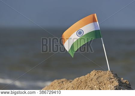 National Table Flag Of India On Sea Background. Flag Of India On Sandy Shore