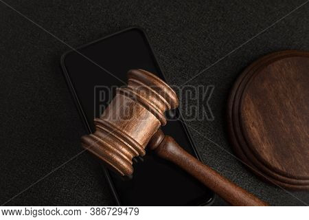 Wooden Judge Gavel On The Smartphone. Court Decision. Rights Holders