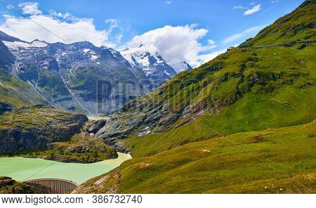 Panoramic view at Pasterze Glacier Grossglockner among austrian Alps mountains summits blue sky clouds.