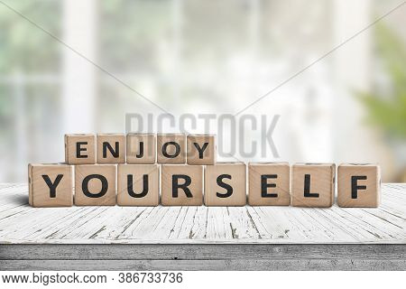 Enjoy Yourself Wriiten On Wooden Blocks In A Bright Room. Cubes With A Positive Phrase On A White De