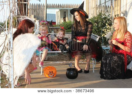 Women and children checking out candy after a dress-up party