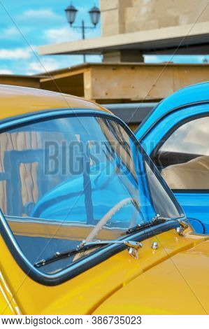 Car Hood And Windshield Of A Yellow Car On The Background Of A Blue Car Close-up