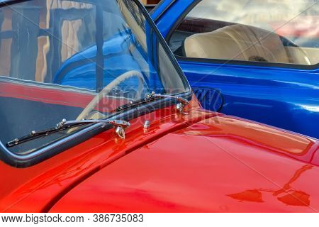 Car Hood And Windshield Of A Red Car On The Background Of A Blue Car Close-up