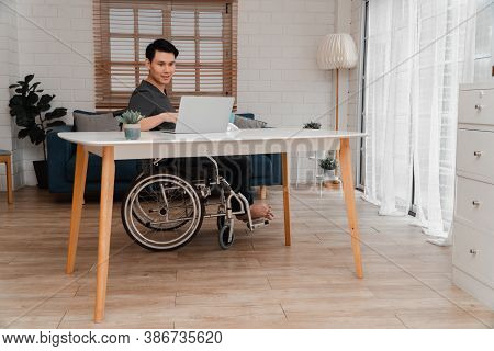 Happy Disabled Asian Man Sitting In A Wheelchair And Working With Computer At Home, The Concept Of T