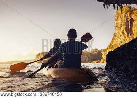 Active Couple Walks By Kayak Or Canoe At Sunset Sea Bay. Krabi Province. Thailand