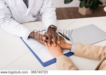 Partial View Of African American Doctor Touching Hands Of Patient Near Insurance Claim Form And Lapt