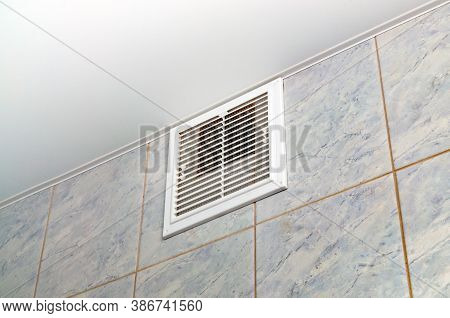 Ventilation In The Bathroom. Close - Up Of The Ventilation Grate On The Tile Wall