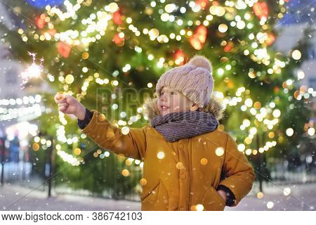 Little Boy Having Fun With His Family On Traditional Christmas Fair. Child Holding Bright Sparkler.