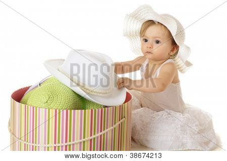 An adorable baby girl looking spacey in her petticoat as she digs into a large, colorful, filled hat box.  On a white background.