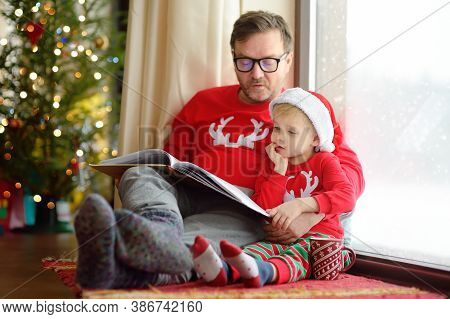 Little Boy Wearing Santa Hat And His Father Are Reading The Book, Drinking Hot Cocoa And Looking Out