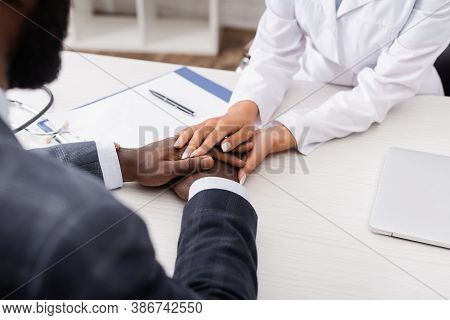 Partial View Of Doctor Touching Hands Of African American Patient Near Clipboad At Workplace