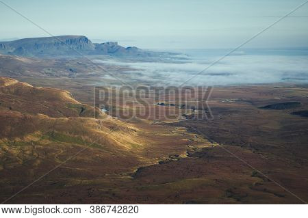 A Top View Of A Autumn Mountain Valley With Winding River And The Sea Covered With Low Clouds At Daw