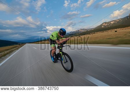 triathlon athlete riding professional racing bike at workout on curvy country road