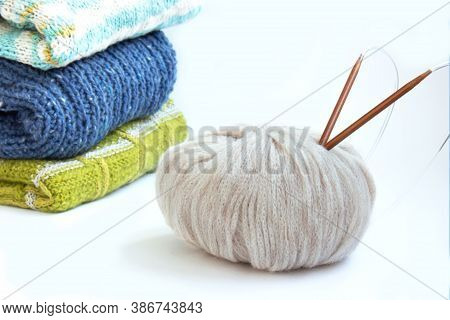 Stack Of Blue, Brown, Green Knitted Sweaters And Knitting Needles With A Ball Of Yarn On A White Bac