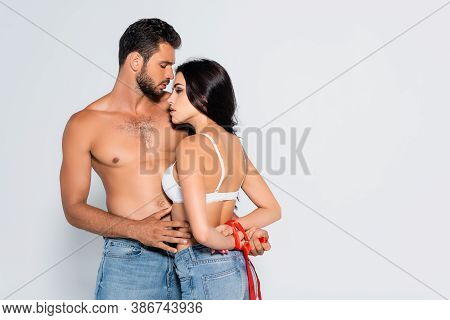 Brunette And Submissive Woman With Tied Hands Near Muscular Man Isolated On White