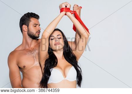 Submissive Woman With Tied Hands And Closed Eyes Near Muscular Man Isolated On White