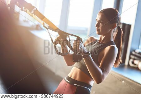 Side View Of A Young Strong And Fit Woman Exercising With Fitness Trx Straps At Gym