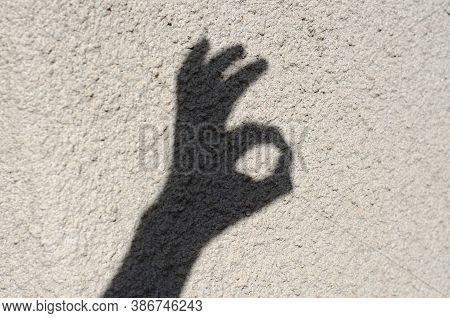 The Shadow Of A Mans Hand On The Wall Shows An Okay Gesture.