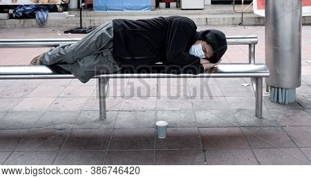 A Poor Homeless Man Sleeps On A Bus Stop Chair There Was A Cup To Put Beggar Because Poverty Asked F