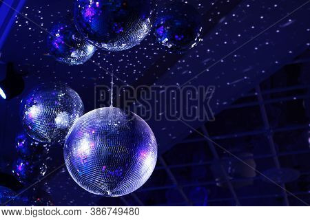 The Concept Of Disco. Light And Music Disco Ball On A Blue Background. A Rotating Disco Ball In A Ni