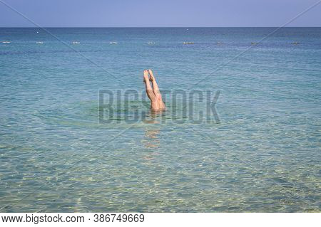 A Woman Plunging In Turquoise Sea Water. Feet Sticking Out Of The Water.