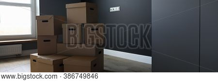 Close-up Of Empty Room With Stack Of Cardboard Boxes. Organized Stuff In Carton. New Apartment Or Ho