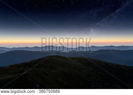 Mountains range against the backdrop of an incredible starry sky. Amazing night landscape with Milky Way. Tourism concept