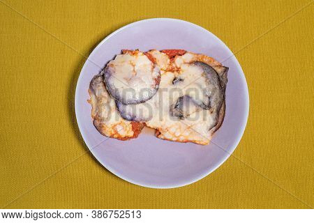 Aubergine Parmigiana Served In A Lilac Colored Dish Placed On A Light Green Table Runner, Food Photo