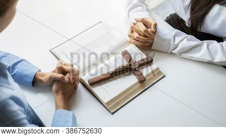 Christian Woman Praying With Hands Together On Holy Bible And Wooden Cross. Woman Pray For God Bless