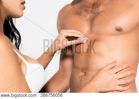 Partial View Of Woman Holding Ice Cube Near Torso Of Shirtless Man Isolated On White