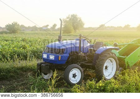 A Farm Blue Tractor Stands On The Field. The Use Of Machines In Agriculture Increases The Speed And