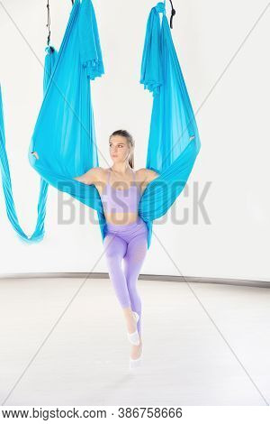 Hatha Aero Fly Yoga Concept. Beautiful Young Female Trainer Showing Stretching Exercises On Blue Ham