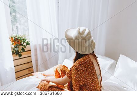 Beautiful Young Woman In White Hat Sitting On Bed Near Window In Sunny Morning. Relaxing Time. High