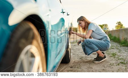 Attractive Young Woman Checking Air Pressure Of Car Tire On Local Road Side While Traveling, Having