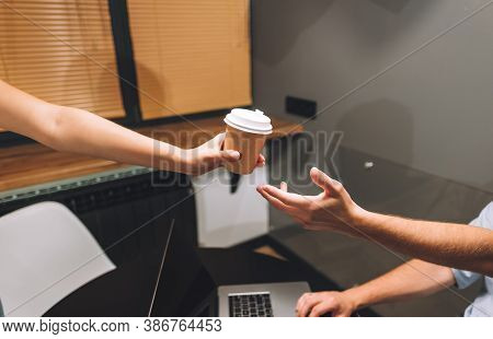 A Colleague Passes A Cup Of Coffee To His Partner While Working On A Project In The Office. High Qua