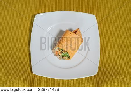 Vegetarian Wrap Served On A White Plate Resting On A Mustard-colored Table Runner, Food Photography